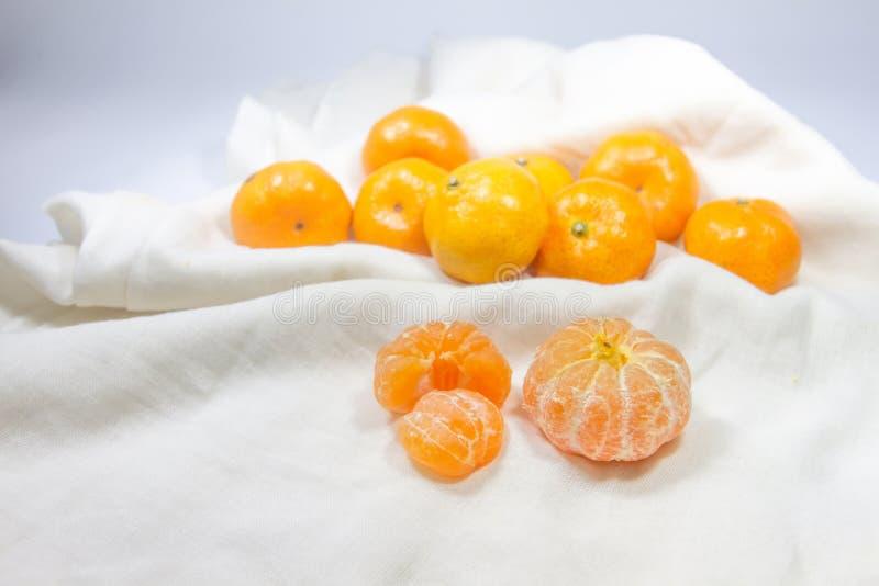Ny apelsinfrukt som är ordnad på vitt tyg som bakgrund arkivfoto
