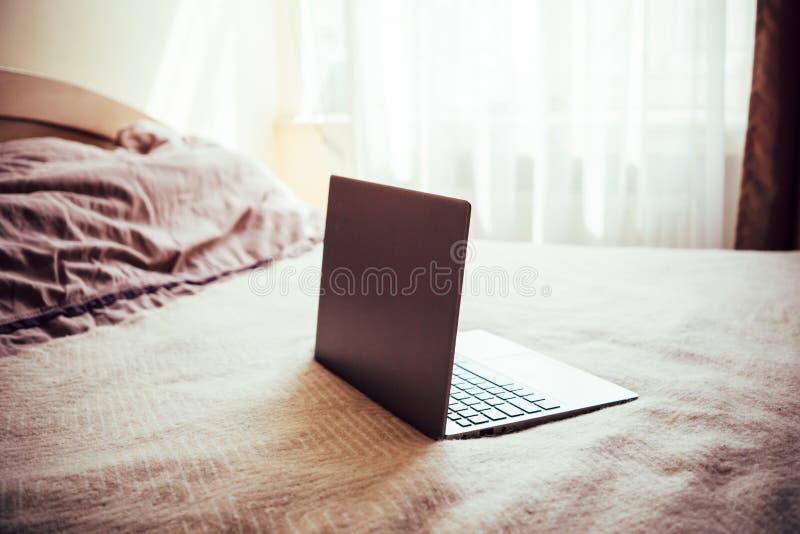 Ny bärbar dator med den tomma skärmen på sängfilten i hem- sovruminre royaltyfria bilder