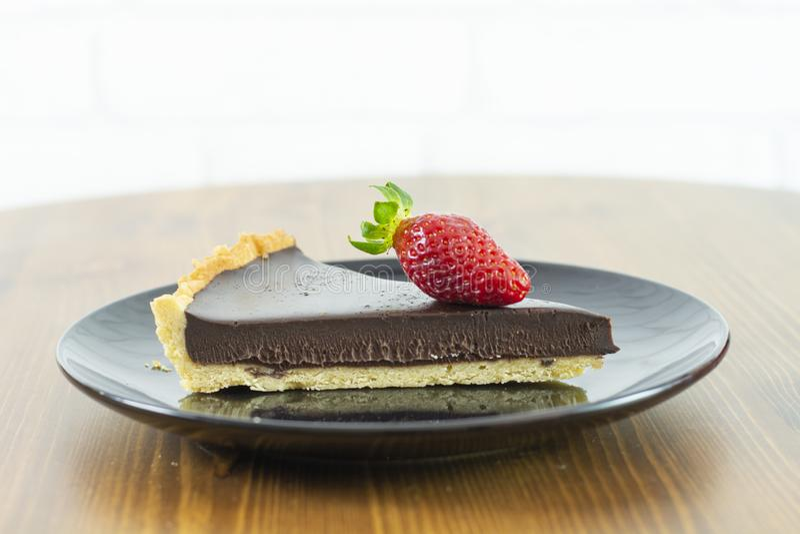 Ny bakad choklad som är syrlig med jordgubben med den svarta plattan arkivfoto