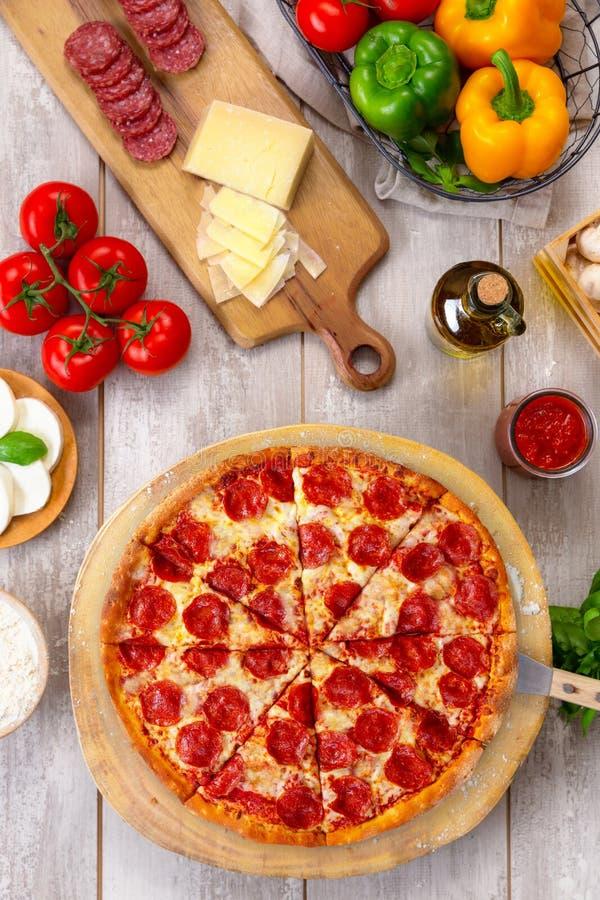 Ny bakad peperonipizza på träbräde och tabellen, med färgrika ingredienser, vertikal över huvudet bästa sikt royaltyfria bilder