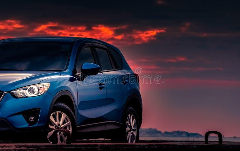 Ny blå SUV bil med sporten och den lyxiga designen som parkeras på den konkreta vägen av havet på solnedgången med dramatiska him fotografering för bildbyråer
