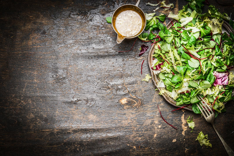 Ny blandad grön sallad med lantlig träbakgrund för olje- dressing, bästa sikt sund mat arkivbild