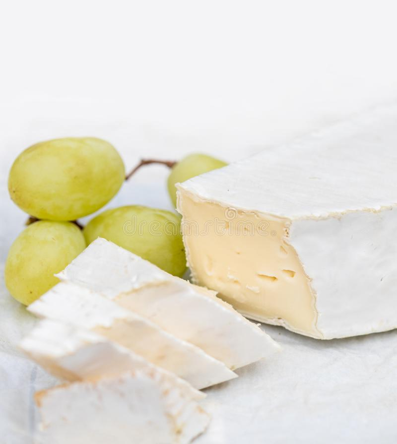 Ny Brie med skivor och druva på vitt lantligt på en uppvakta arkivbild
