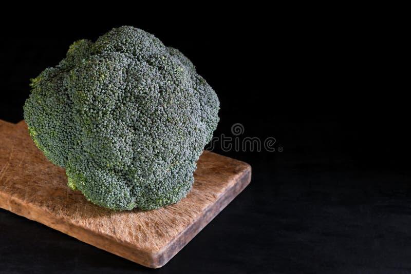 Ny broccoli på en skärbräda på en svart bakgrund, lantlig stil, mörk tangent sund mat arkivbild