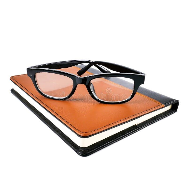 Ny brun läderanteckningsbokdagbok med svarta exponeringsglas som isoleras på vit bakgrund royaltyfri foto