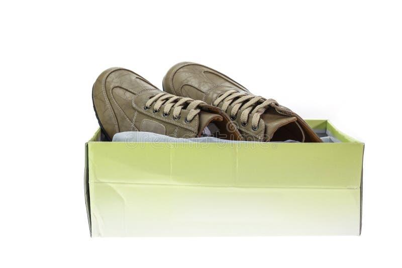 Ny brun sko i asken som isoleras på vit arkivfoton