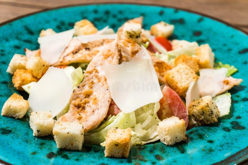 Ny caesar sallad i grön platta på trätabellen arkivbild