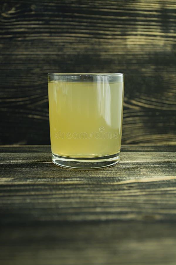 Ny citronjuice i ett exponeringsglas p? en m?rk tr?bakgrund Riktig n?ring royaltyfri fotografi
