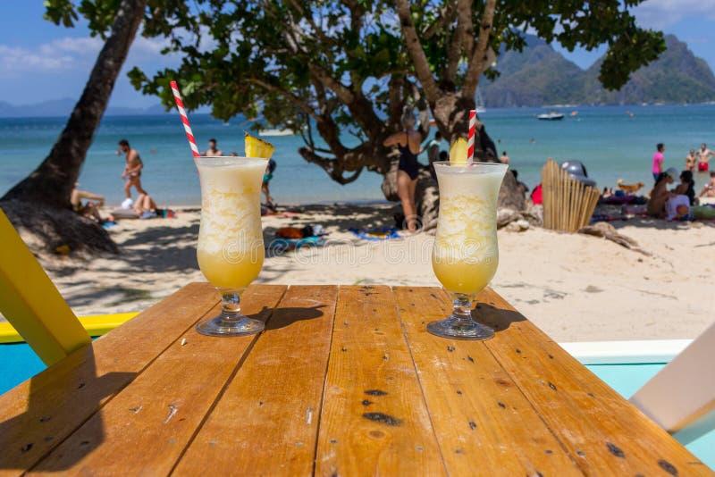 Ny coctail för alkohol två på stranden Kall pinacolada på seascapebakgrund Par av kalla ananascoctailar med sugrör arkivfoton