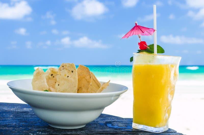 Ny coctail med orange fruktsaft och nachos på tabellen på den tropiska exotiska karibiska stranden arkivbilder