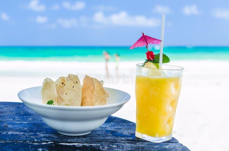Ny coctail med orange fruktsaft och nachos på tabellen på den tropiska exotiska karibiska stranden royaltyfria bilder
