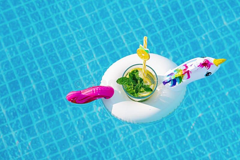 Ny coctailmojito på den uppblåsbara vita enhörningleksaken på simbassängen h?rligt barn f?r kvinna f?r begreppsp?lsemester royaltyfria foton