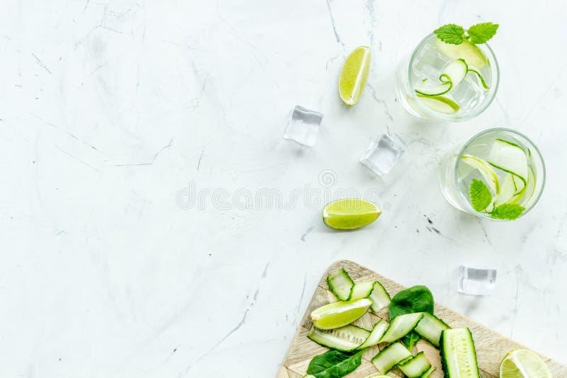 Ny drink med limefrukt, gurkan och is på vit åtlöje för bästa sikt för bakgrund upp arkivfoto