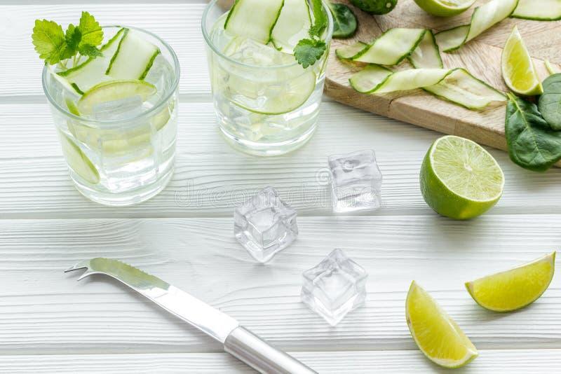 Ny drink med limefrukt, gurkan och is p? vit bakgrund royaltyfri foto