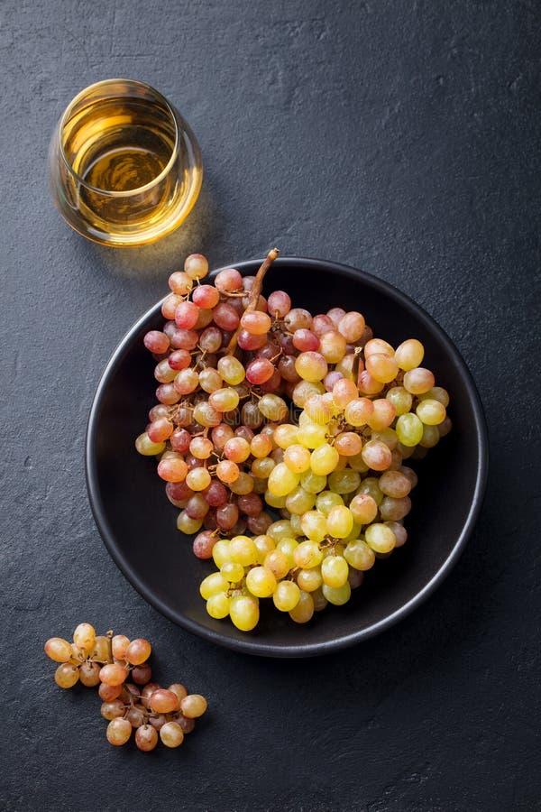 Ny druva i bunke med vitt vin i exponeringsglas på en svartstenbakgrund Top besk?dar royaltyfria foton
