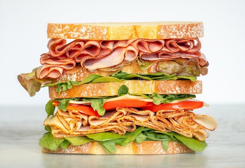 Ny dubbel i lager smörgås med skinka, grönsallat, tomater, ost på ett rostat brödbröd m?nga bakgrundsklimpmat meat mycket arkivbilder