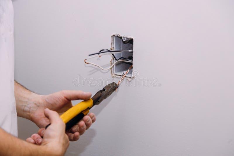 Ny elektrisk installation, hålighetask, strömbrytare och elektriska kablar på väggen, renovering under konstruktionsbegrepp royaltyfria bilder
