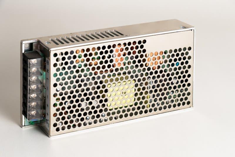 Ny enhet - strömförsörjning för omformare och industriell utrustning på en grå bakgrund fotografering för bildbyråer