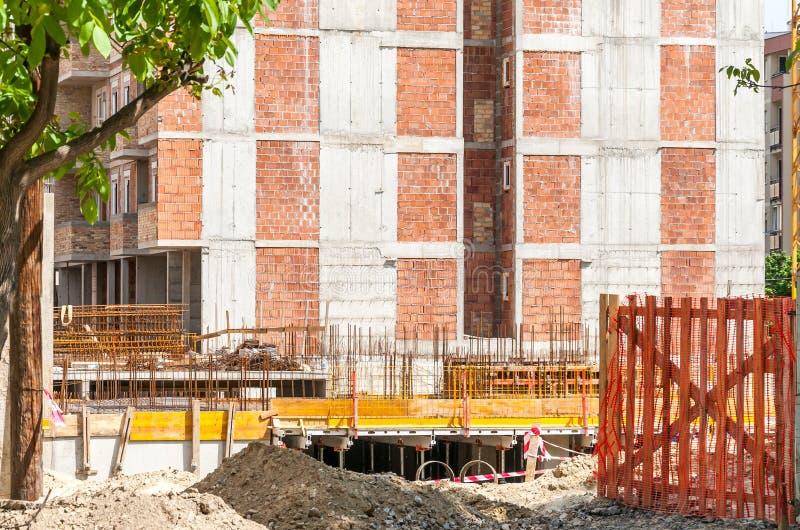 Ny för konstruktionsplats för bostads- byggnad ingång med porten av säkerhetsnätstaketet med sikt på betong- och metallreinforcem royaltyfri fotografi