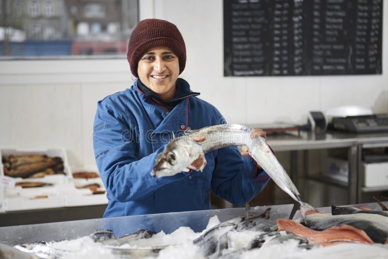 Ny fisk presentated av fishdealeren fotografering för bildbyråer