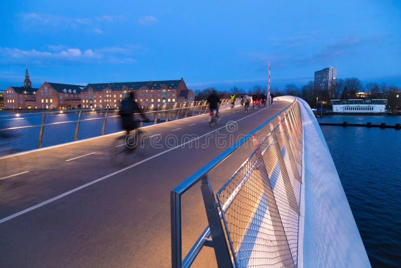 Ny fotgängare och cykelbro i Köpenhamn Kvällsljus royaltyfri fotografi