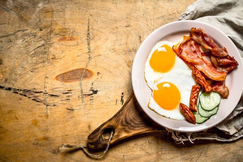 Ny frukostplatta baconägg stekte tomater royaltyfri foto