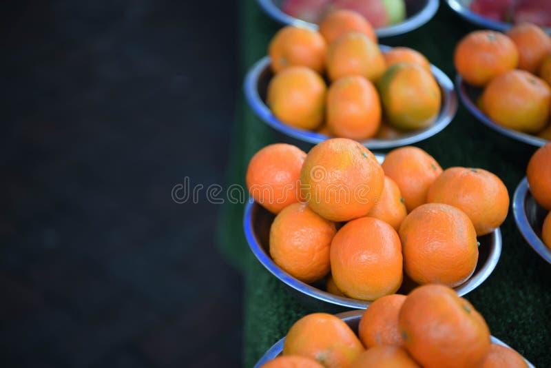 Ny frukt av ljusa kulöra apelsiner i bunkar med mörk bakgrund royaltyfria bilder