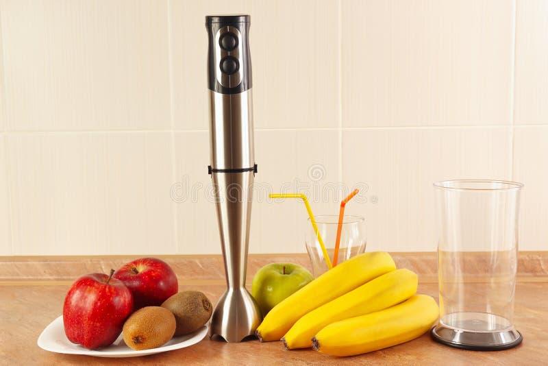 Ny frukt, exponeringsglas och blandare som förbereder hemlagade smoothies royaltyfria bilder
