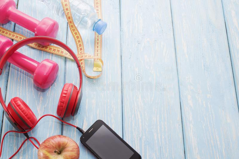 Ny frukt med hantlar på en träcountertop, kopieringsutrymme, bantar, och det sunda matbegreppet Hörlurar och telefon Musik i spor arkivfoto