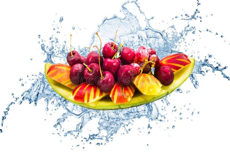 Ny frukt på idérikt färgstänkvatten i isolerad bakgrund royaltyfri foto