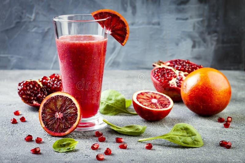 Ny fruktsaft eller smoothie för Detox i exponeringsglas med blodapelsiner, gräsplaner, granatäpple Hemlagad uppfriskande fruktdry royaltyfria bilder