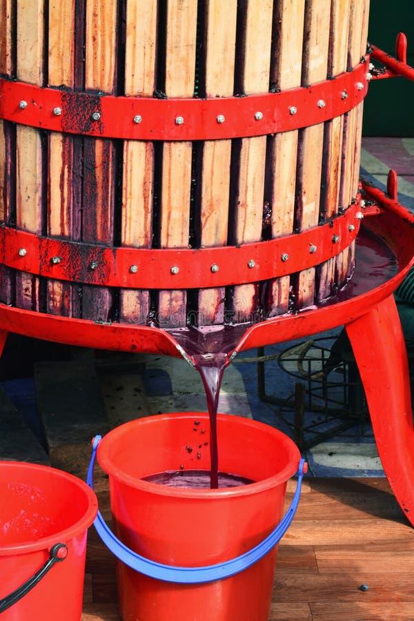Ny fruktsaft för den röda druvan flödar in i en hink från en korgpress fotografering för bildbyråer