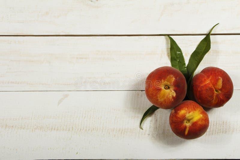Ny fruktsaft för persika med nya persikor på en vit bakgrund Bästa sikt, kopieringsutrymme Ny fruktsaft med persikan äta som är s royaltyfria bilder