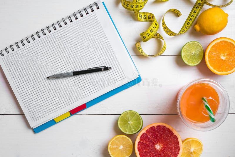Ny fruktsaft i exponeringsglas från citrusfrukter - citron, grapefrukt, apelsin, anteckningsbok med blyertspennan på vit träbakgr arkivfoto