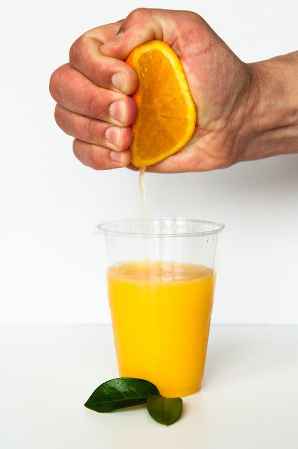 ny glass fruktsaftorange Handen pressar fruktsaft från en apelsin Runda orange skivor på en vit bakgrund Citrus fotografering för bildbyråer