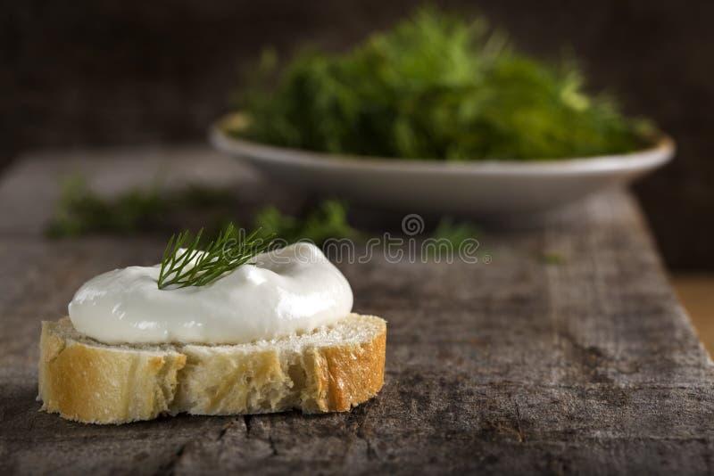 Ny gräddost på brödskiva med dill på trä arkivfoto