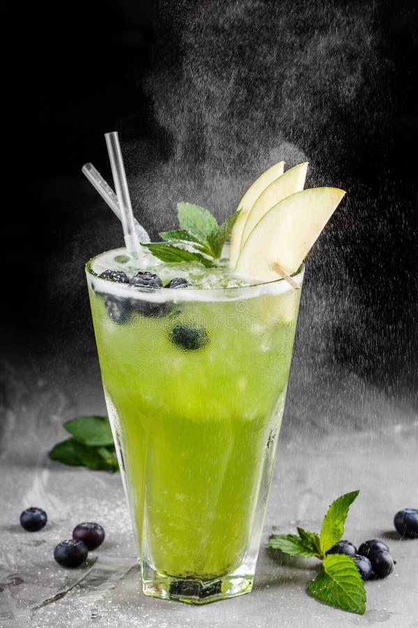 Ny grön äpplelemonad med blåbär och is i exponeringsglas över mörk bakgrund arkivbilder