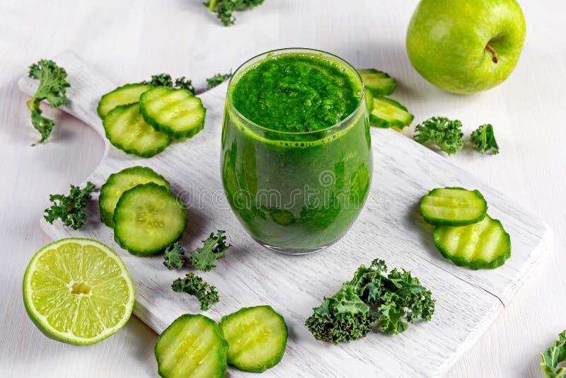Ny grön smoothie med grönkål, gurka, limefrukt, äpple, persilja på det vita brädet royaltyfria bilder