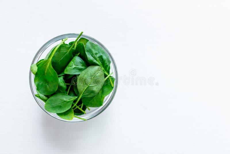 Ny grön spenat lämnar i exponeringsglasbunke på den vita tabellen royaltyfri bild