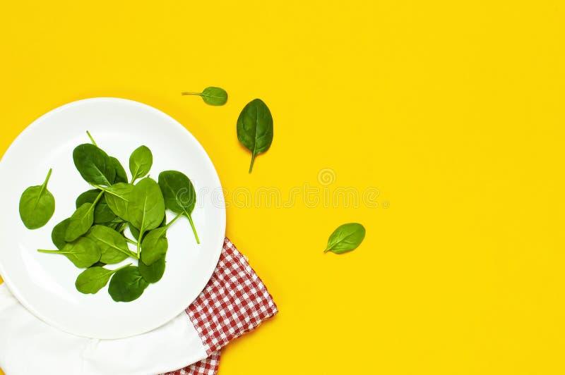 Ny grön spenat lämnar på en vit plattakökshandduk på utrymme för kopia för bästa sikt för ljus gul bakgrund plant lekmanna- Behan royaltyfri bild