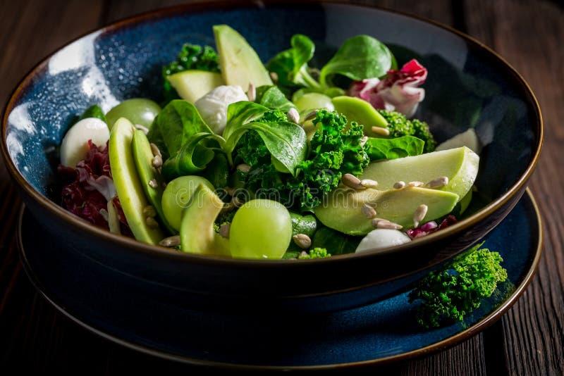Ny grönkålsallad med avokadot, grönsallat och druvan fotografering för bildbyråer