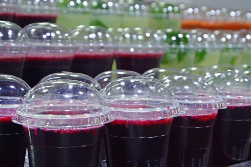 Ny granatäpplefruktsaft och mojito i plast- exponeringsglas på räknaren En kall drink säljs på en marknad i Jerusalem, Israel arkivbilder