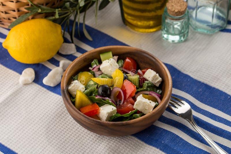 Ny grekisk sallad i bunke med gurkan och löken för ost för olivtomatfeta på textilservett royaltyfri foto