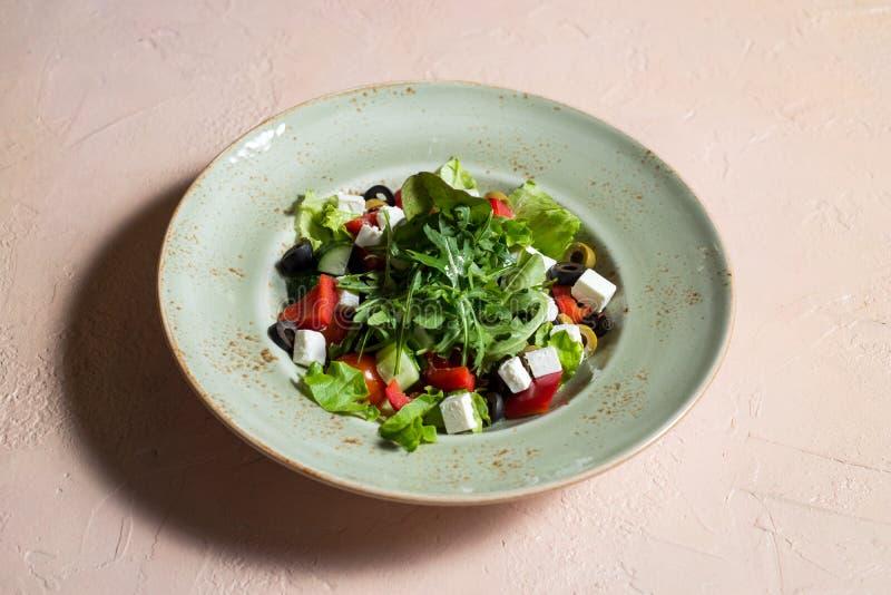 Ny grekisk sallad i bunke med svart oliv, tomaten, fetaost, gurkan och l?ken p? den vita tr?tabellen close upp arkivbilder