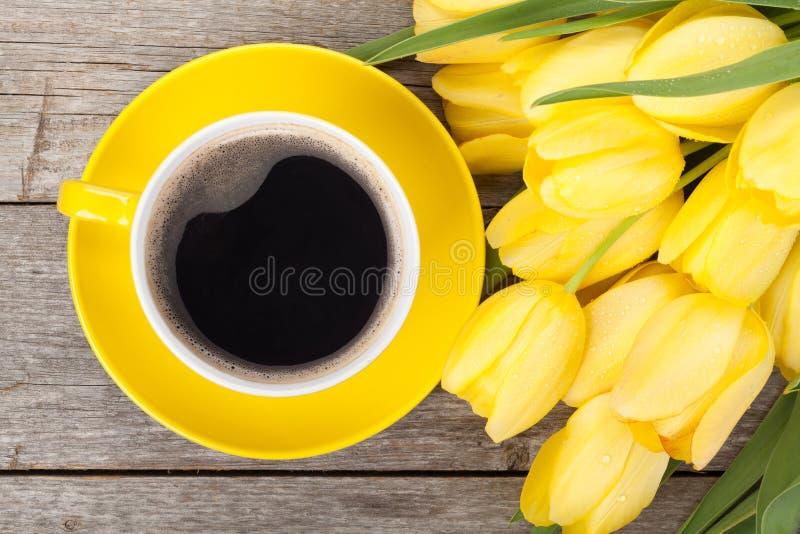 Ny gul tulpanbukett och kaffekopp royaltyfri bild