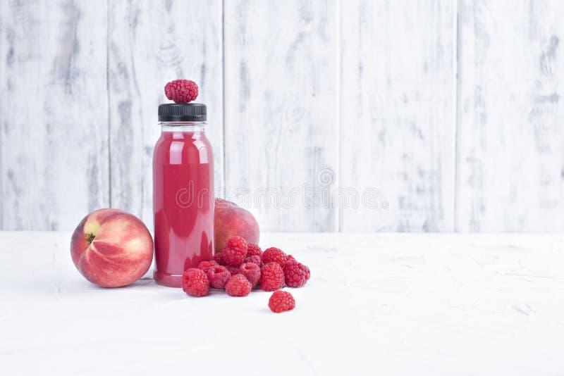 Ny hallon, persikor och fruktsaft i en plast- flaska detox Vit bakgrund kopiera avstånd royaltyfri foto