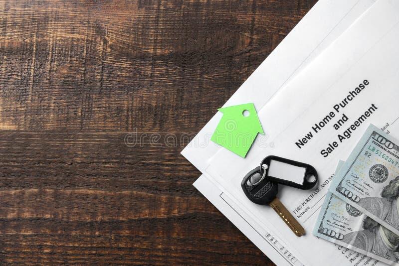 Ny hem- köp- och försäljningsöverenskommelse Tangent med keyringen och mellanrum och pengar på en brun trätabell Begrepp av att k fotografering för bildbyråer