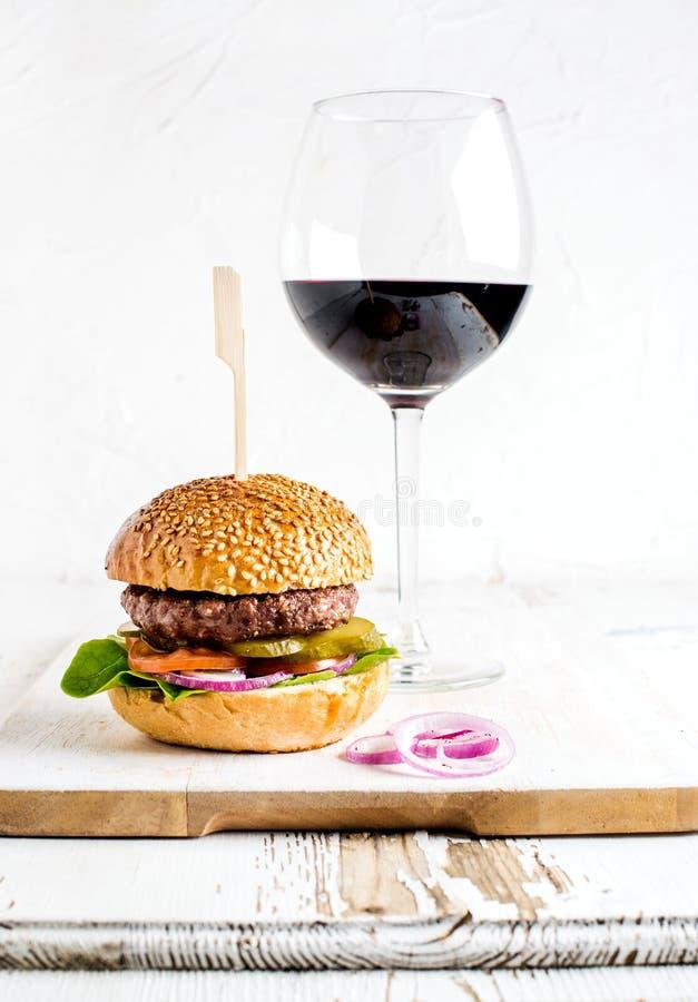 Ny hemlagad hamburgare på träportionbräde med lökcirklar och exponeringsglas av rött vin arkivbild