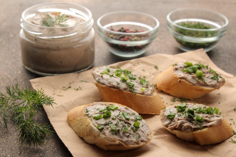 Ny hemlagad pate för feg lever med gräsplaner på bröd på en mörk bakgrund En smörgås royaltyfri bild