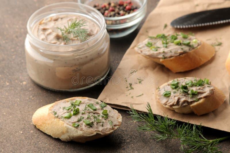 Ny hemlagad pate för feg lever med gräsplaner på bröd på en mörk bakgrund En smörgås arkivfoton